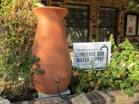 "Rainwater barrel and ""This yard is helping to conserve our water supply"" sign at the Barton Springs Edwards Aquifer Conservation District  Photo courtesy of Robin Gary, BSEACD"